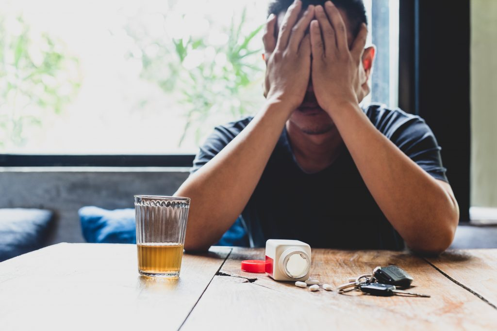 A man sitting at a table needing help with drug addiction and depression.